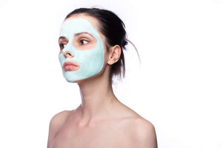 woman in cosmetic mask on her face, white background