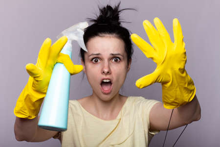 Woman wiping surface with cloth wearing apron and rubber gloves