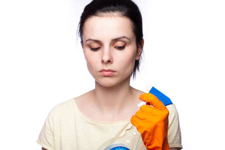 Beautiful happy housewife with rubber gloves and cleaning material on white Stock Photo