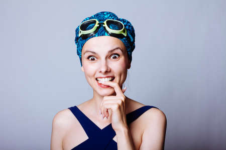 smile woman swimmer, in a swimming cap, glasses and a swimsuit, gray background