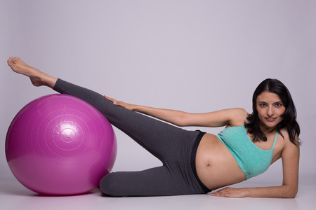 Healthy pregnant lady excercising  with a pilates ball