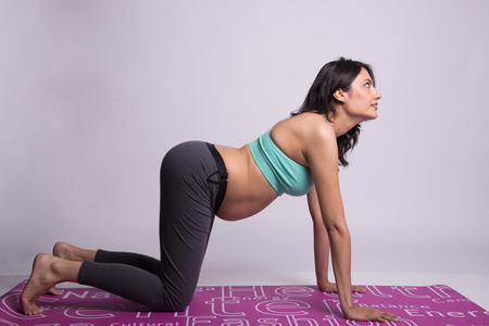 Pregnant lady in yoga postures Stock Photo