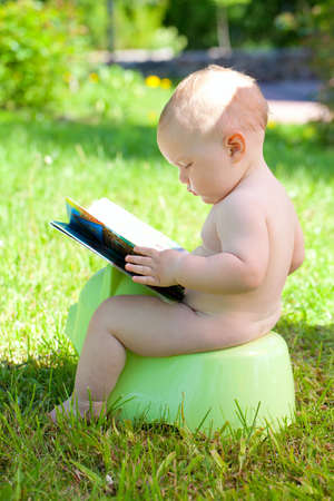 naked child: baby outdoors is sitting on his potty and reading his book