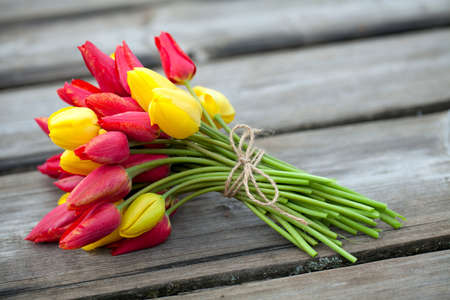 tied yellow and red tulips on wooden surface photo