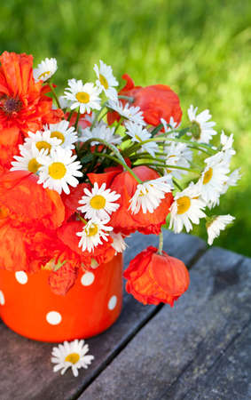 chamomiles and poppy flowers on wooden table photo