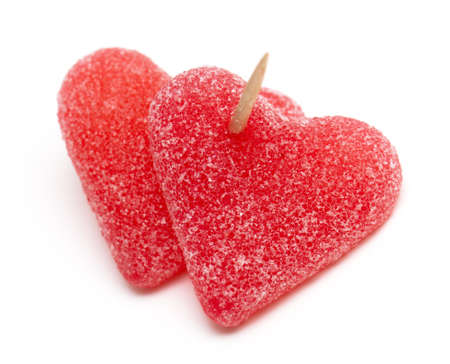 two heart-shaped candies atached to each other with a toothpick on white photo