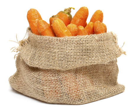carrots in a burlap bag isolated on white background photo