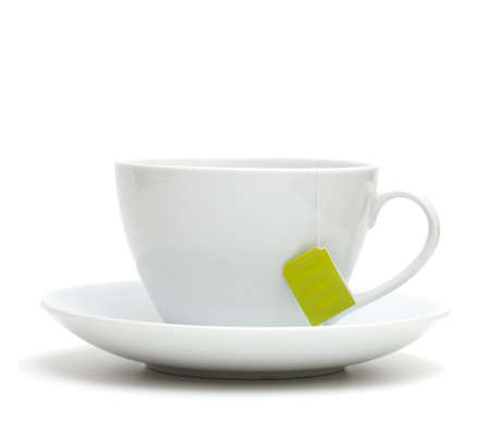 Cup of tea with tea bag (blank label) on white background photo