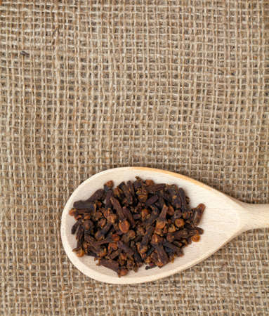 cloves in wooden spoon on sackcloth photo