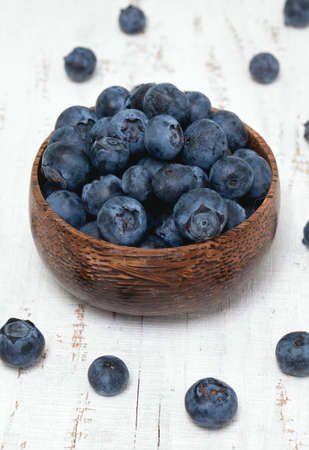 bowl full of blueberries on wooden table photo