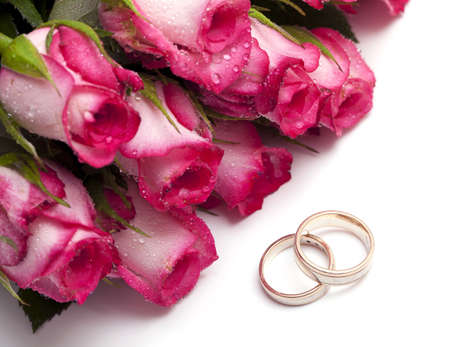 pink roses with droplets and wedding rings isolated on white photo