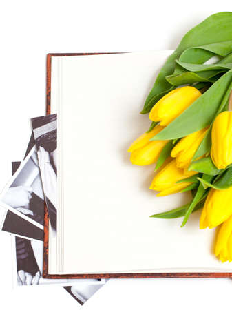yellow tulips lying on book with black and white photographs photo
