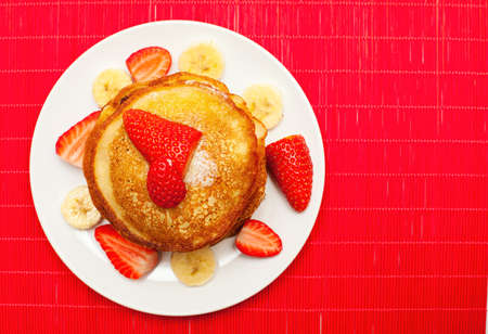 golden buttermilk pancakes with strawberry and banana on red photo