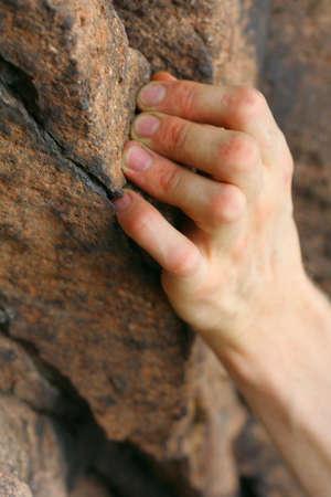 rock climbers hand on a rock photo