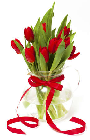 stalk flowers: red tulips in a vase with a red ribbon isolated on white