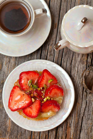 strawberry cake and cup of tea on wooden table photo