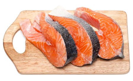 pieces of raw salmon on cutting board on white background photo