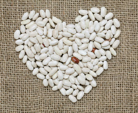 heart shape made of white beans on sackcloth photo