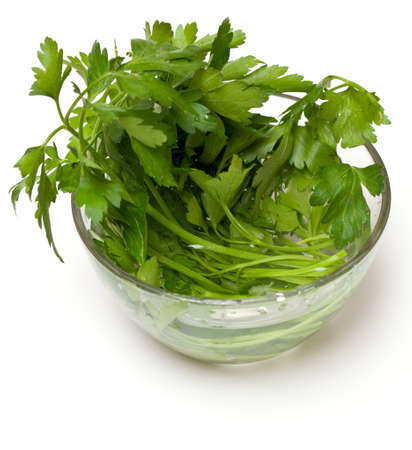 bunch of parsley in a glass bowl isolated on white photo