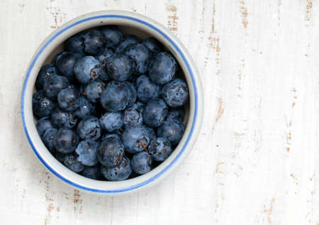 bowl with fresh blueberries on wooden table Stock Photo