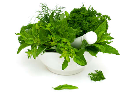 medical herbs: mortar with herbs isolated on white