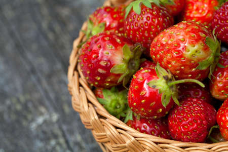 strawberries in basket on wooden table photo