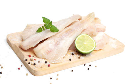 frozen pollock (pallock) and spices on wooden board isolated Stock Photo