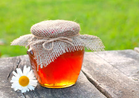 jar with honey on garden table photo