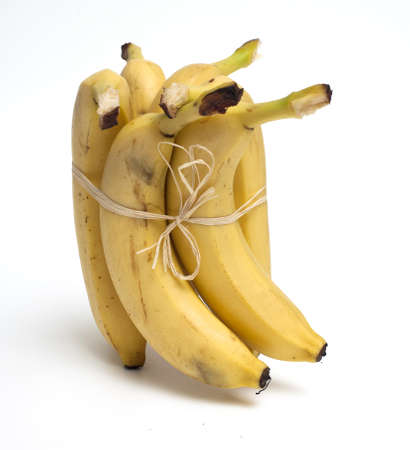 tied bananas over white photo