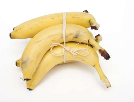 tied bananas over white photo