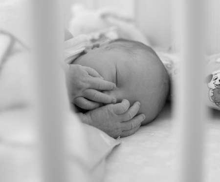 black and white  photo of newborn sleeping in his crib photo