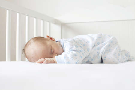 newborn lying on his tummy in crib photo