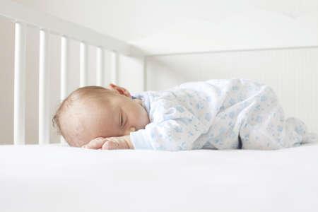 newborn lying on his tummy in crib Stock Photo