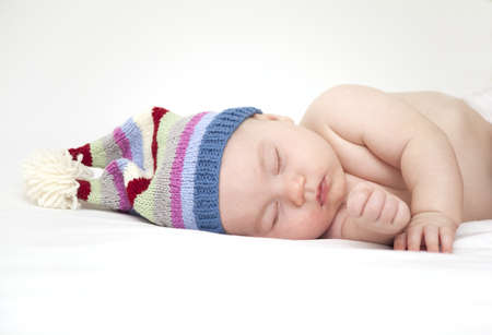 sleeping baby in a funny striped hat Stock Photo