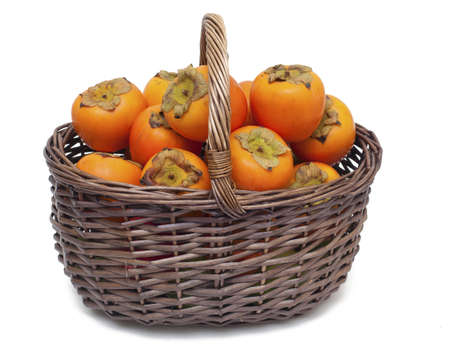ebenaceae: basket full of persimmons isolated on white background Stock Photo