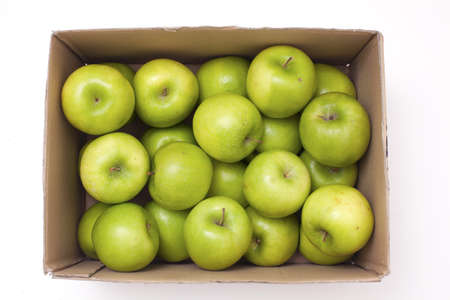 box with green apples isolated on white photo