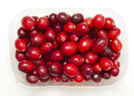 cranberries in plastic box isolated over white photo