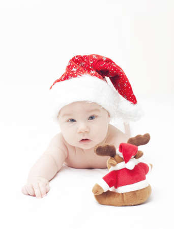 4 months belly: babyin Santas hat looking at reindeer isolated Stock Photo