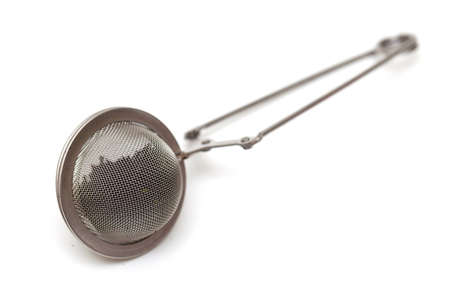 tea filter: tea infuser filled with tea isolated Stock Photo