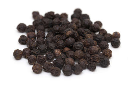 pile of black peppercorns isolated on white photo