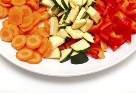 cut vegetables on white plate, top view photo