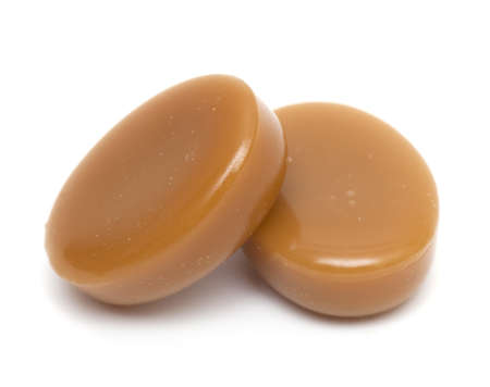 dulce de leche: Cerca de dos dulces de caramelo en el fondo blanco