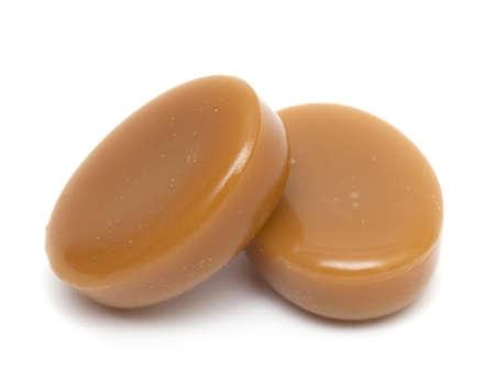 toffee: close-up van twee karamel snoepjes op een witte achtergrond
