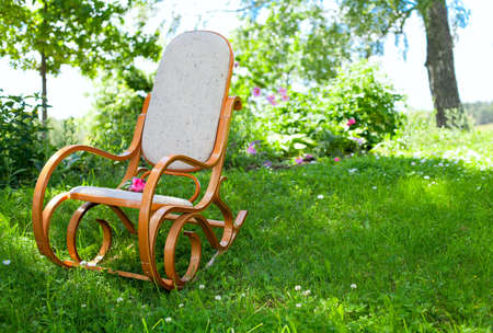 rocking chair with pink rose in spring garden photo