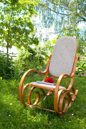 rocking chair with rose and laptop in spring garden photo