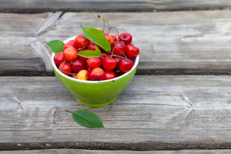 bowl with cherries on wooden table photo
