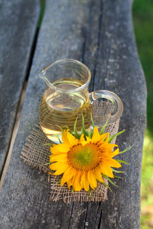 sunflower and sunflower oil on wooden table photo
