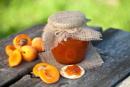 fresh apricot jam on wooden table photo