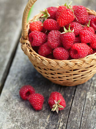 fresh raspberry in a basket on wooden table photo