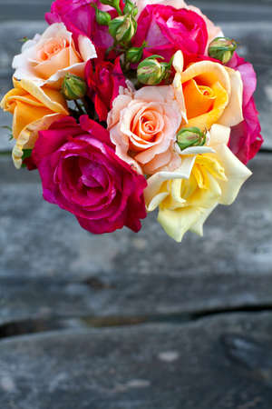 beautiful bouquet of different roses on wooden table photo